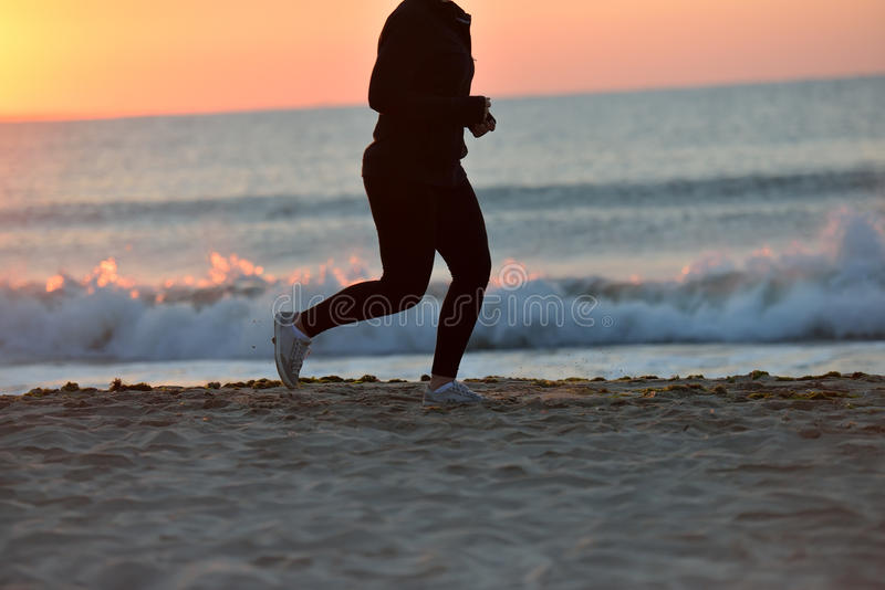 Silueta de una chica joven que corre solamente a lo largo de la playa del imagen de archivo libre de regalías
