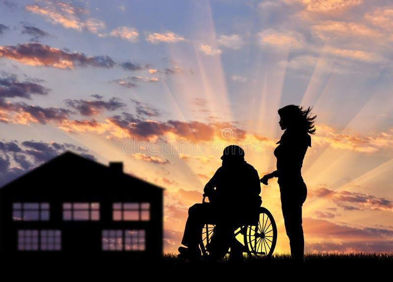 Silueta de una enfermera que cuida para una persona discapacitada en una silla de ruedas imágenes de archivo libres de regalías
