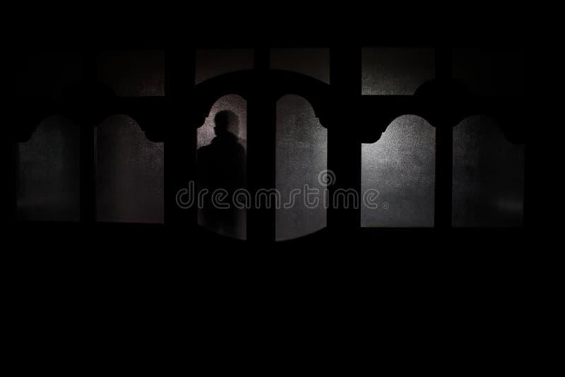 Silueta de una figura desconocida de la sombra en una puerta a través de una puerta de cristal cerrada La silueta de un ser human libre illustration