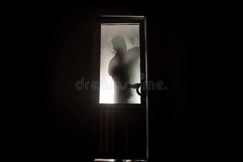 Silueta de una figura desconocida de la sombra en una puerta a través de una puerta de cristal cerrada La silueta de un ser human fotos de archivo libres de regalías