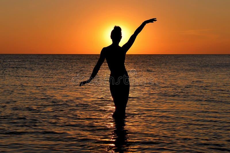 Silueta de una figura femenina misteriosa en el fondo de la puesta del sol del mar fotos de archivo