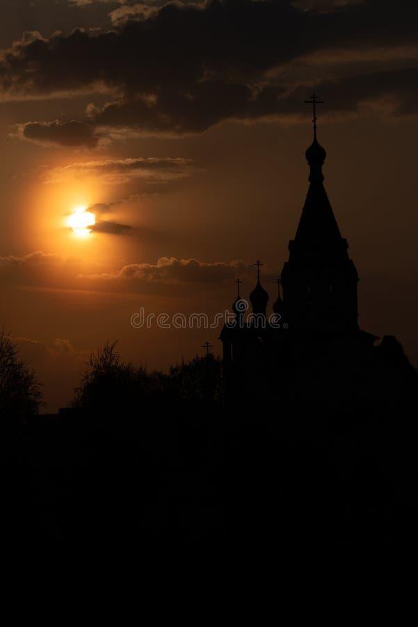 Silueta de una iglesia hrestian con un campanario contra un cielo de la puesta del sol, inundada con los rayos anaranjados del so foto de archivo