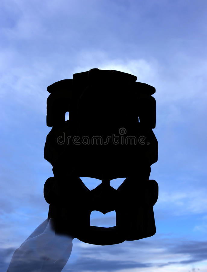 Silueta de una máscara y de un cielo azul imagen de archivo