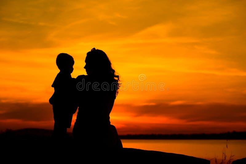 Silueta de una madre joven con su pequeño niño fotografía de archivo libre de regalías