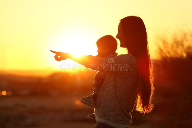 Silueta de una madre que señala horizonte con su bebé fotos de archivo libres de regalías