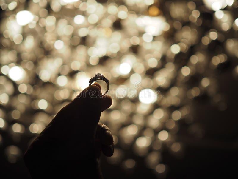 Silueta de una mano masculina que lleva a cabo un anillo de diamante grande con el fondo amarillo de la luz del bokeh Foco selecc fotografía de archivo