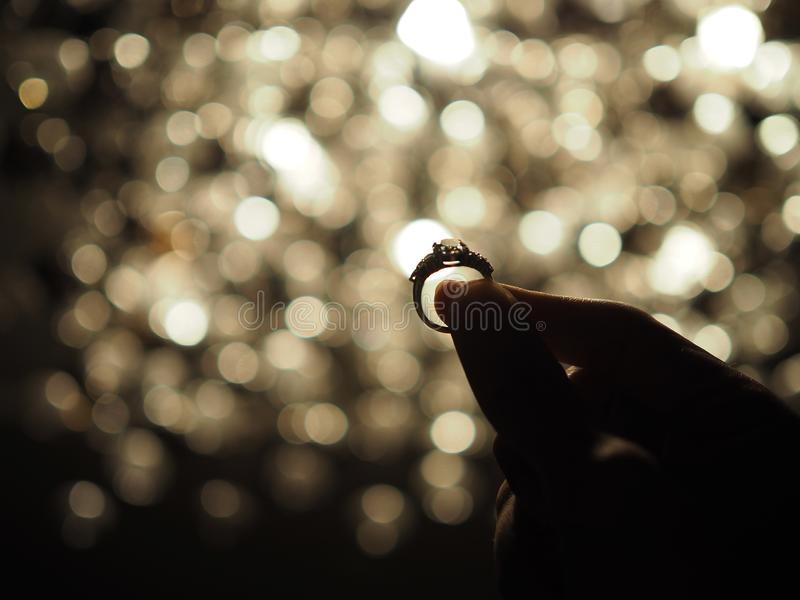 Silueta de una mano masculina que lleva a cabo un anillo de diamante grande con el fondo amarillo de la luz del bokeh Foco selecc imagenes de archivo