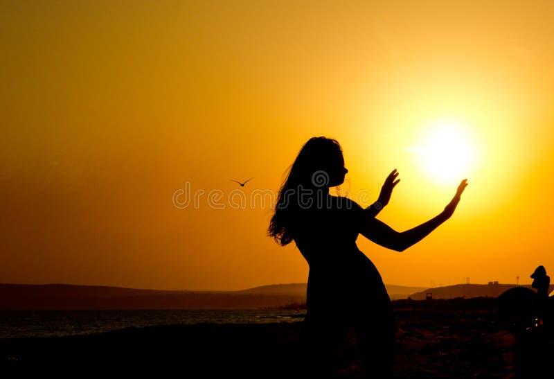 silueta de una muchacha con la cintura fina y las manos extendidas al sol en la puesta del sol fotografía de archivo