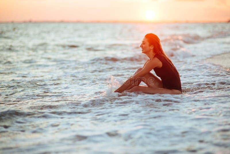 Silueta de una muchacha en el agua en la puesta del sol foto de archivo