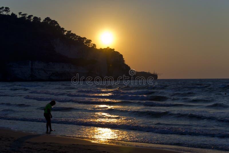 Silueta de una muchacha en la playa durante puesta del sol para el concepto de las vacaciones y de las vacaciones de verano foto de archivo libre de regalías