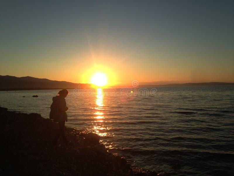 Silueta de una muchacha en la puesta del sol en el lago Baikal foto de archivo