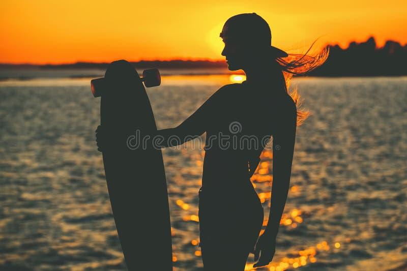 Silueta de una muchacha hermosa, atractiva del inconformista en los tatuajes que se oponen con un longboard a la puesta del sol imagenes de archivo