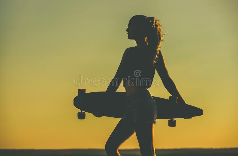 Silueta de una muchacha hermosa, atractiva del inconformista en los tatuajes que se oponen con un longboard a la puesta del sol fotos de archivo libres de regalías