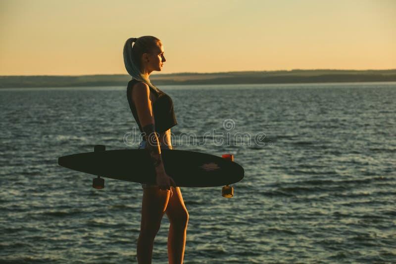Silueta de una muchacha hermosa, atractiva del inconformista en los tatuajes que se oponen con un longboard a la puesta del sol fotografía de archivo libre de regalías