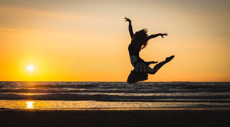Silueta de una muchacha hermosa feliz del bailarín en la puesta del sol imagen de archivo