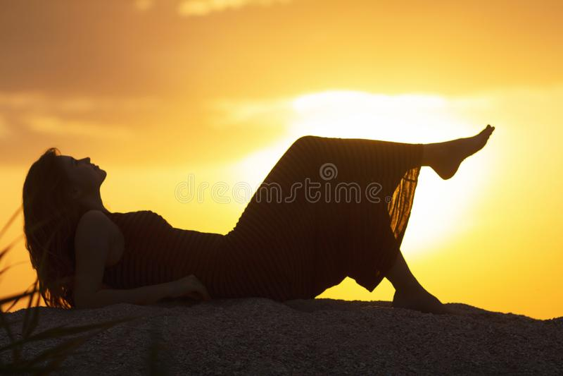 Silueta de una muchacha hermosa joven que miente en un vestido en la arena y que disfruta de la puesta del sol, la figura de una  imágenes de archivo libres de regalías