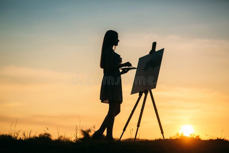 Silueta de una muchacha La muchacha del blonde pinta una pintura en la lona con la ayuda de las pinturas Un caballete de madera g fotos de archivo libres de regalías