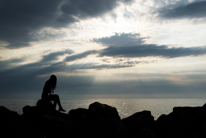 Silueta de una muchacha que mira hacia el horizonte, sentándose en las piedras de la costa foto de archivo