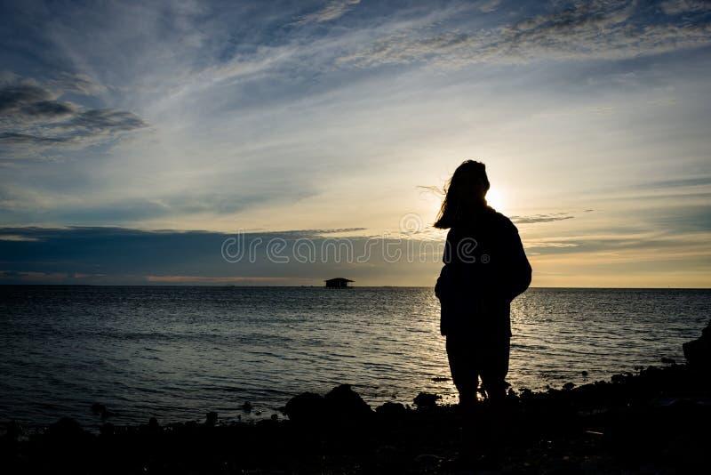 Silueta de una muchacha que se coloca solamente en la costa con el cielo hermoso en el fondo imagen de archivo libre de regalías