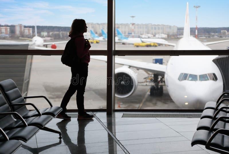 Silueta de una muchacha turística en el terminal de aeropuerto fotos de archivo