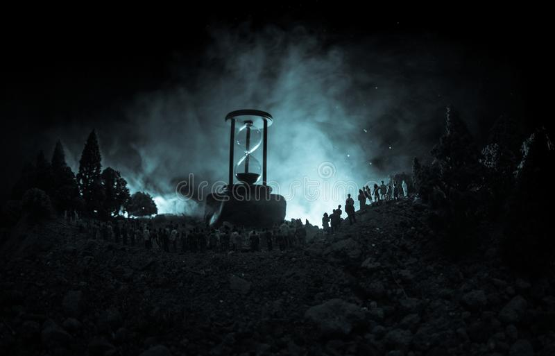 Silueta de una muchedumbre grande de gente en bosque en la noche que se opone a un reloj de arena grande con los haces luminosos  fotos de archivo libres de regalías