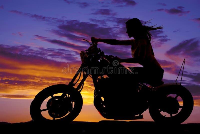 Silueta de una mujer en soplar del viento de la motocicleta imagen de archivo libre de regalías