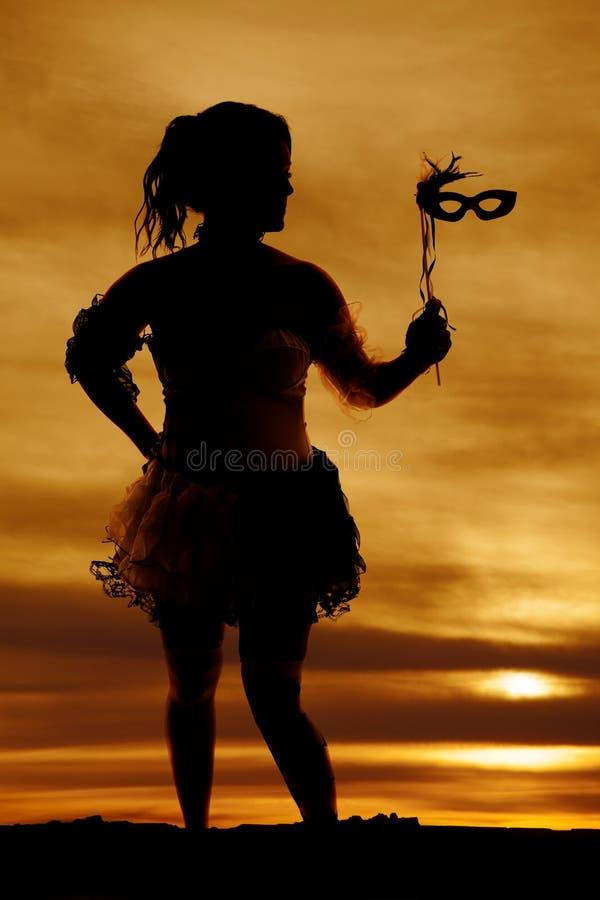 Silueta de una mujer en un traje con una máscara al lado fotografía de archivo libre de regalías