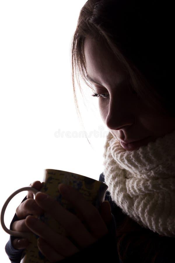 Silueta de una mujer joven con una taza fotografía de archivo