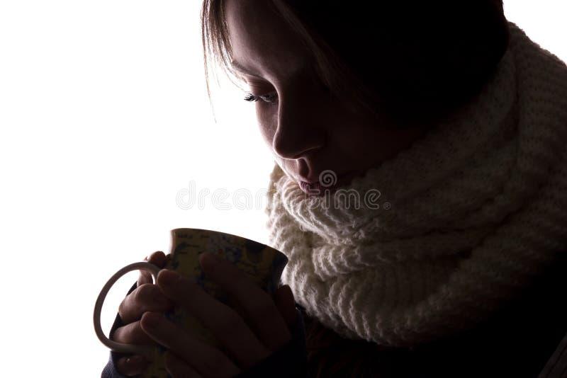 Silueta de una mujer joven con una taza fotos de archivo libres de regalías