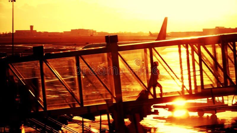 Silueta de una mujer joven que camina en un puente de cristal del jet Embarque de un avión en el aeropuerto por la tarde imagenes de archivo