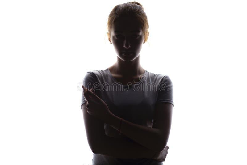Silueta de una mujer joven seria y confiada que mira muchacha recta, hermosa en un fondo aislado blanco, belleza del concepto foto de archivo libre de regalías