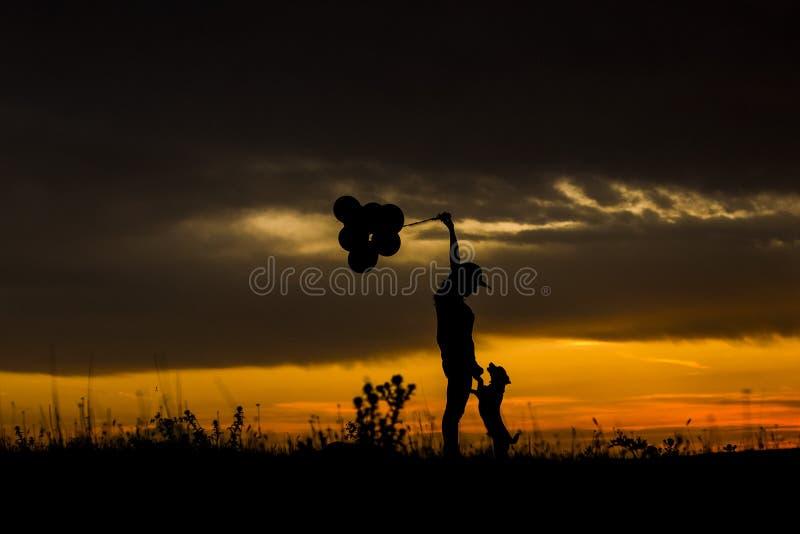 Silueta de una mujer joven y de su perro en la puesta del sol outdoors Ella es globos de las tenencias Amor para el concepto de l foto de archivo libre de regalías