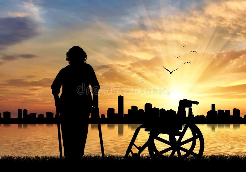 Silueta de una mujer mayor en las muletas en un fondo de la puesta del sol del mar urbano y de la silla de ruedas fotos de archivo libres de regalías