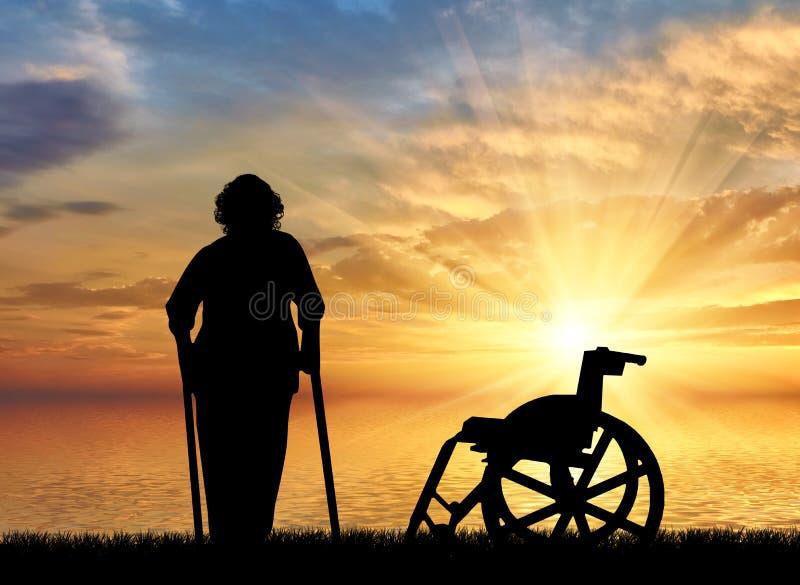 Silueta de una mujer mayor en las muletas en un fondo de la puesta del sol y de la silla de ruedas del mar imágenes de archivo libres de regalías