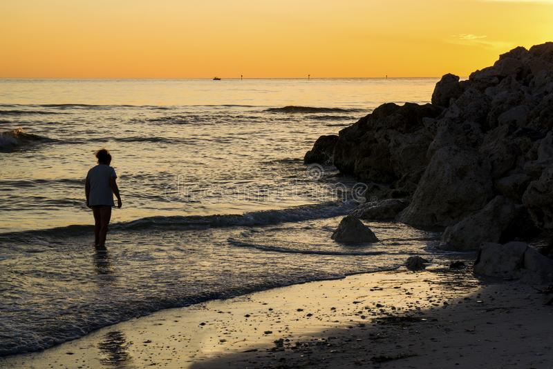 Silueta de una mujer que camina a través de la resaca cerca de St Pete Beach, la Florida foto de archivo libre de regalías