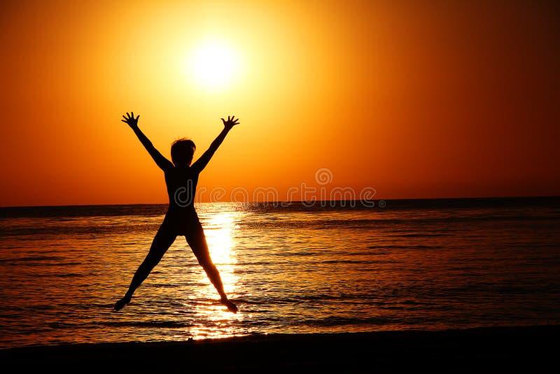Silueta de una mujer de salto contra la perspectiva del sol poniente sobre el mar fotos de archivo