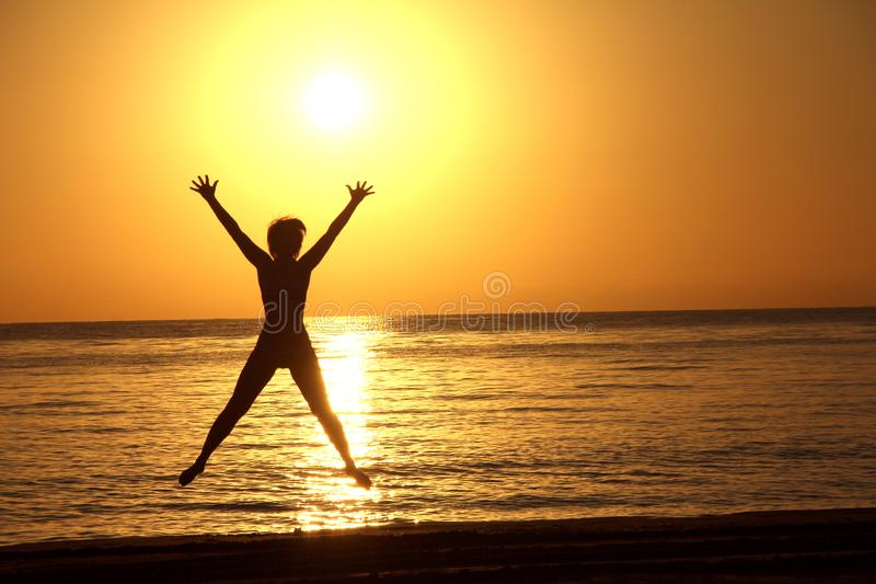 Silueta de una mujer de salto contra la perspectiva del sol que sube sobre el mar imagen de archivo libre de regalías