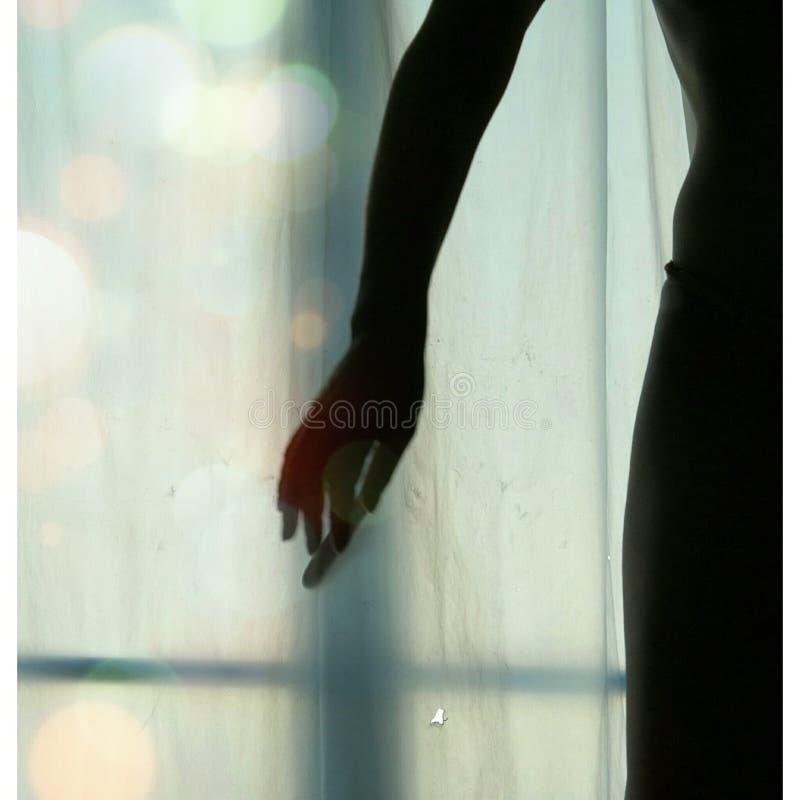 Silueta de una mujer sobre una ventana fotos de archivo libres de regalías