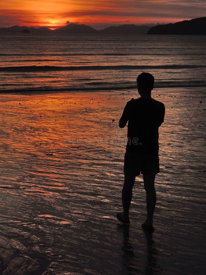 Silueta de una persona observando puesta del sol positiva tranquila sobre el mar en Tailandia, playa del Ao Nang, provincia de Kr fotografía de archivo libre de regalías