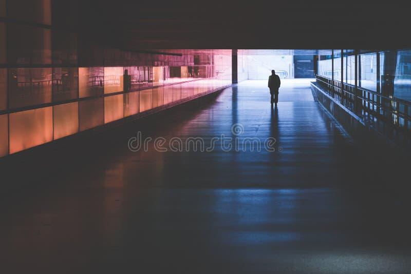 Silueta de una persona que camina en un túnel oscuro imagen de archivo