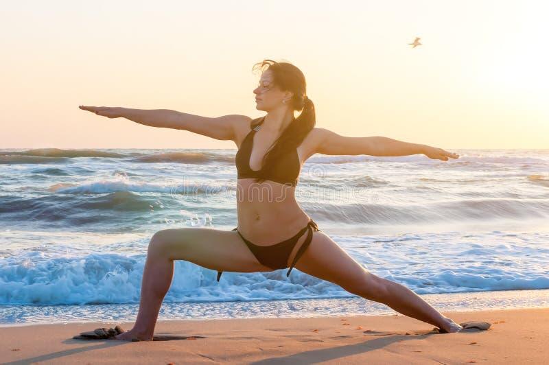 Silueta de una yoga practicante de la mujer joven en la playa en la salida del sol Deporte, concepto de la salud fotos de archivo libres de regalías