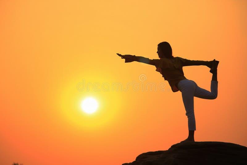 Silueta de una yoga practicante de la mujer en una roca imagen de archivo