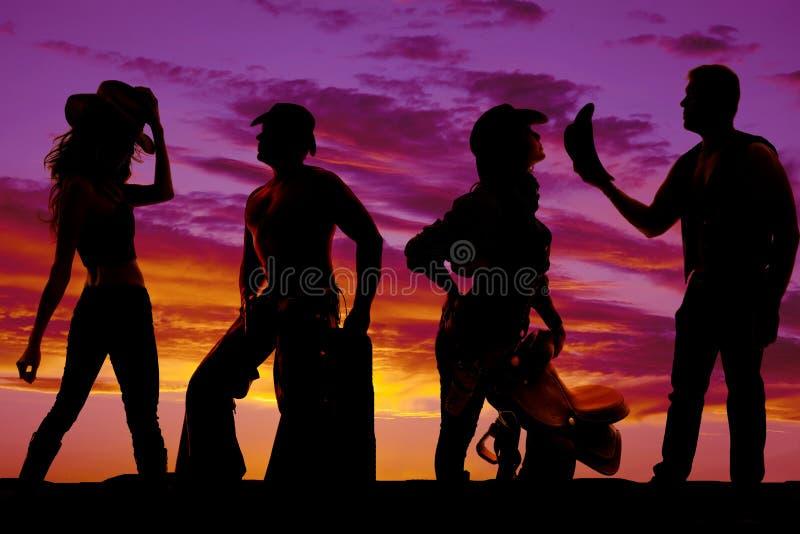 Silueta de vaqueros y de vaqueras junto en la puesta del sol imagen de archivo
