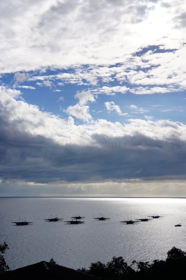 Silueta de varios pequeños barcos que derivan en el océano fotografía de archivo