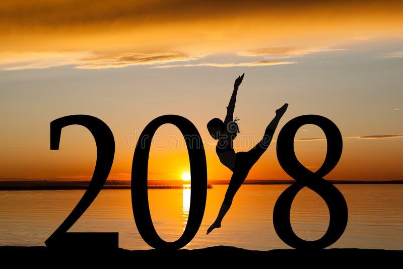 Silueta del Año Nuevo 2018 del baile de la muchacha en la puesta del sol de oro fotografía de archivo libre de regalías