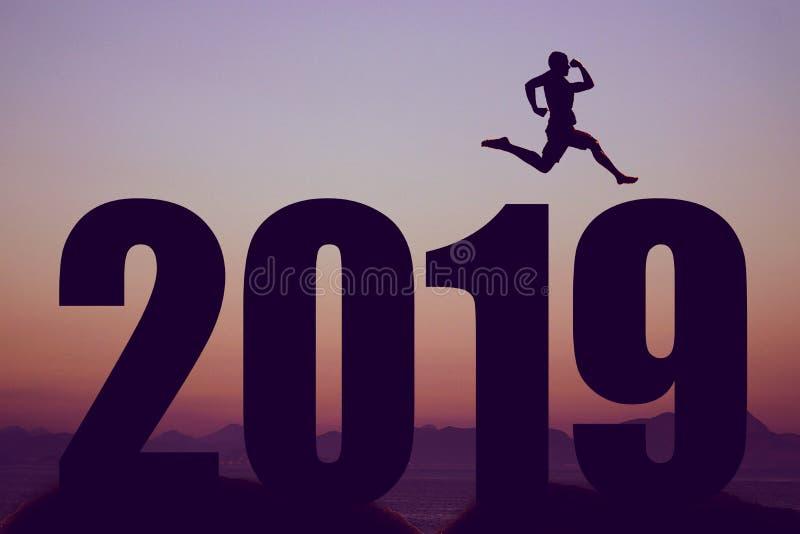 Silueta del Año Nuevo 2019 con el hombre de salto como símbolo para los cambios fotografía de archivo