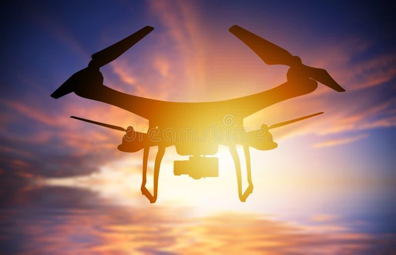 Silueta del abejón con el vuelo de la cámara digital en un cielo de la puesta del sol stock de ilustración