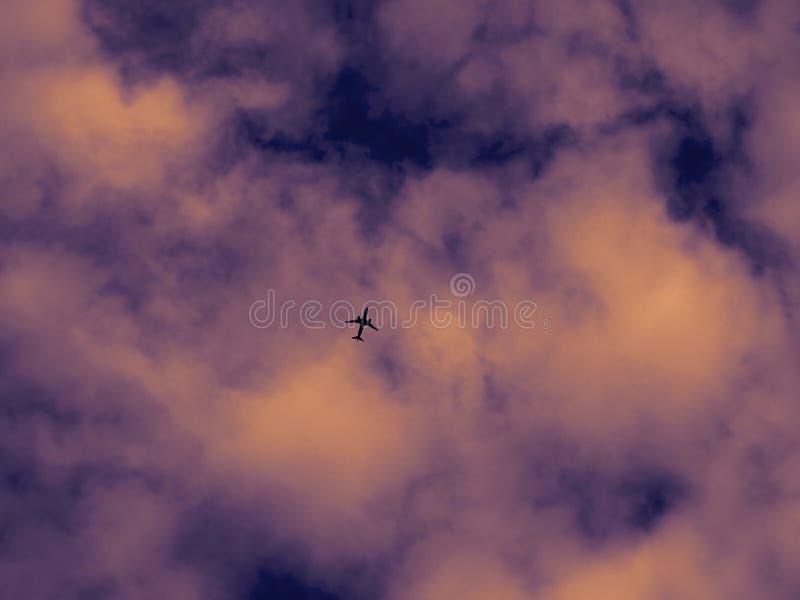 Silueta del aeroplano en un fondo de los colores irreales cielo y nubes dramáticos foto de archivo libre de regalías