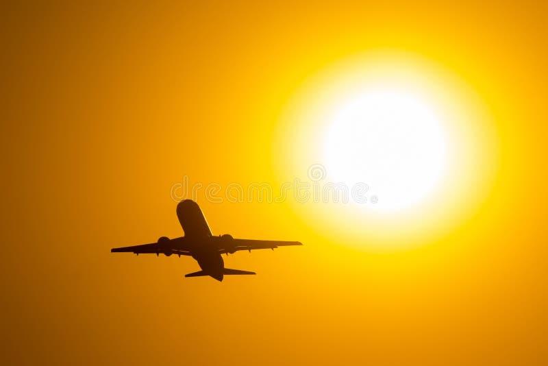 Silueta del aeroplano que saca durante la puesta del sol, moscas cerca del disco del sol foto de archivo libre de regalías