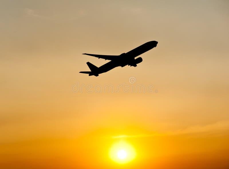 Silueta del aeroplano sobre puesta del sol fotografía de archivo